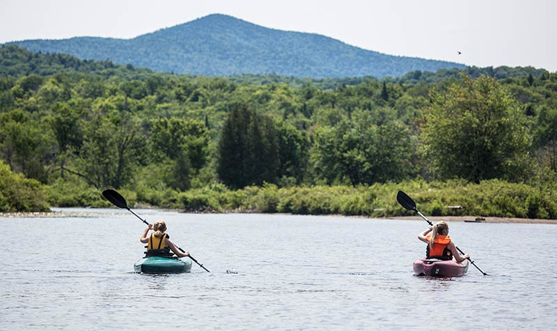Two women kayaking on lake with mountains - Photo Courtesy of Regional Office of Sustainable Tourism