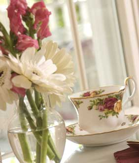 Cup of tea by a vase of flowers